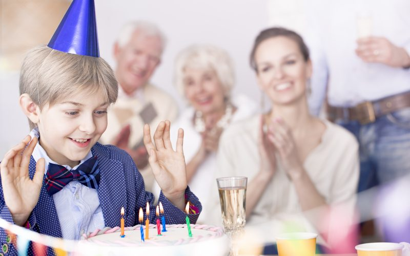 Happy family and boy making birthday wish
